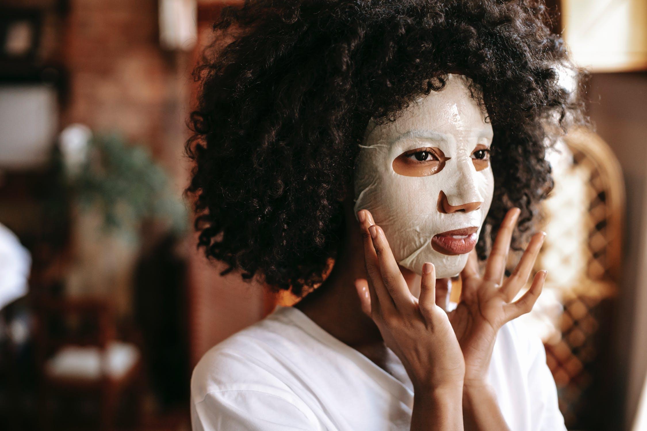 Black woman applying sheet mask