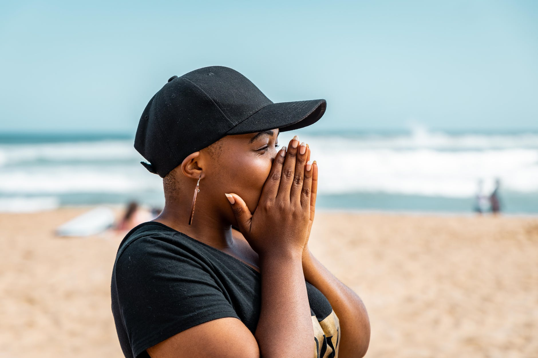 Black woman covering her face at beach