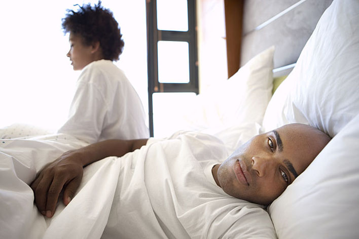 Young couple lying in bed, woman sitting up in background