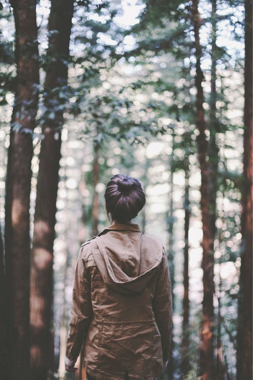 girl walking alone in the woods