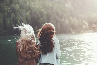 Two female friends standing near lake