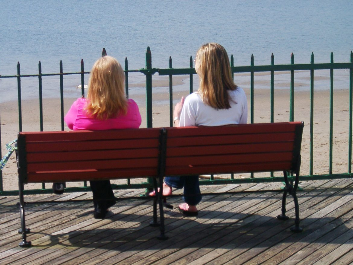 Friends sitting on a bench near water