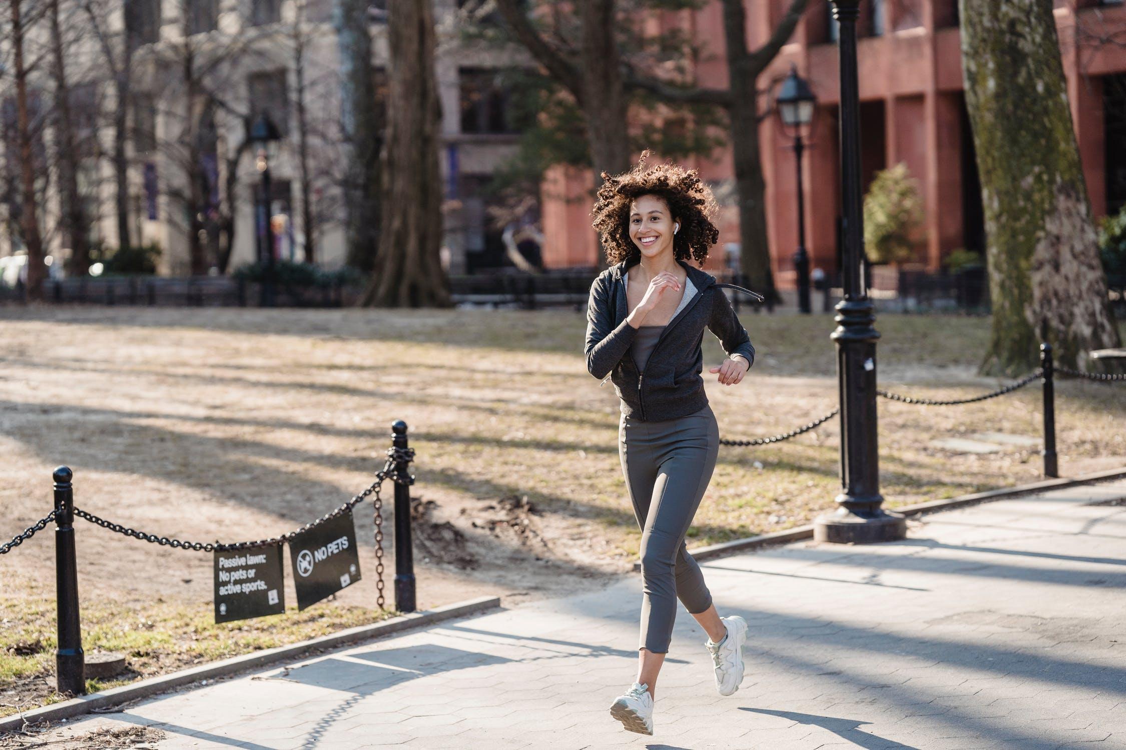 Black sportswoman jogging in park