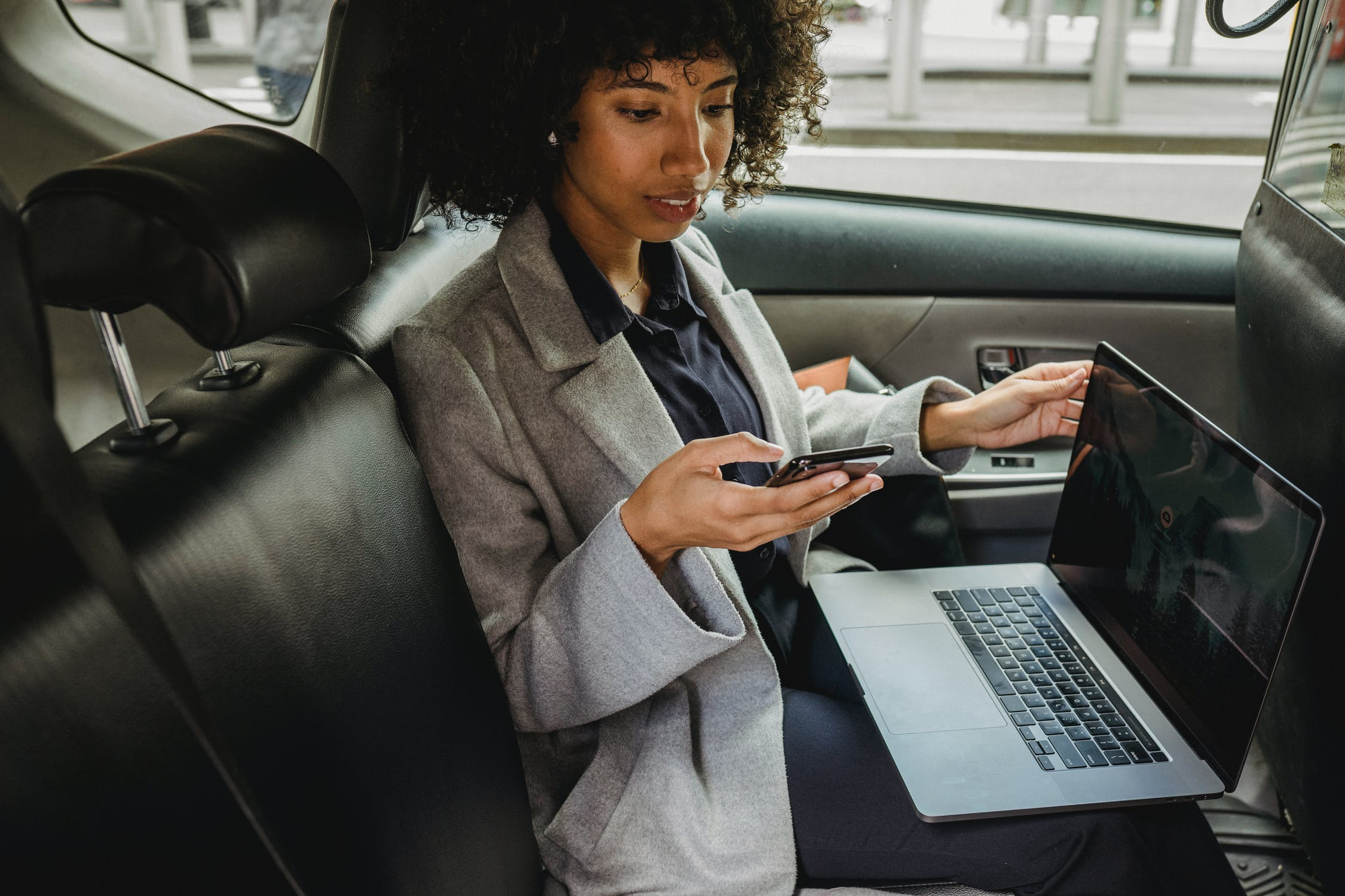 Black woman holding smartphone in backseat of car