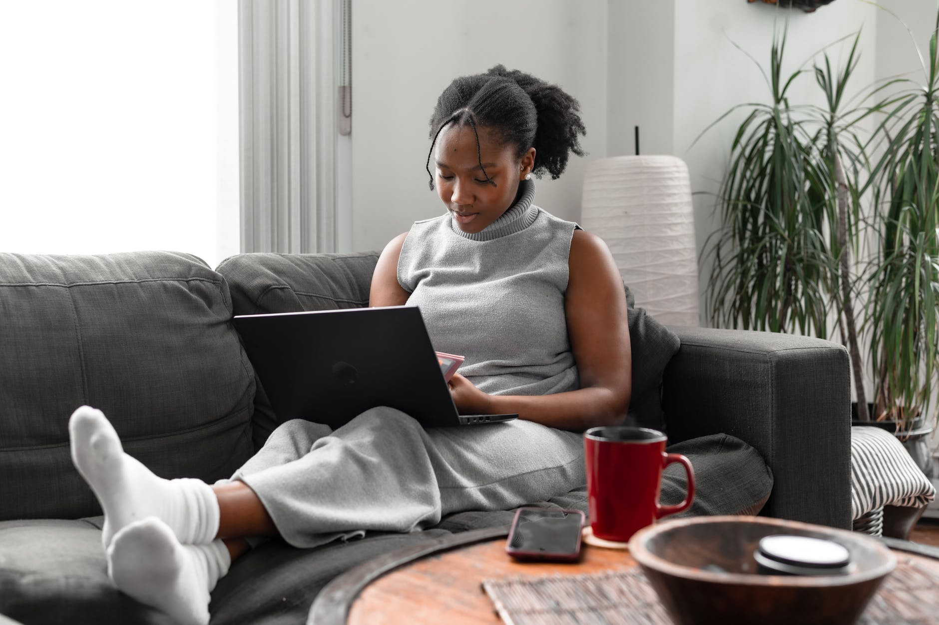 Black woman sitting on couch working on laptop