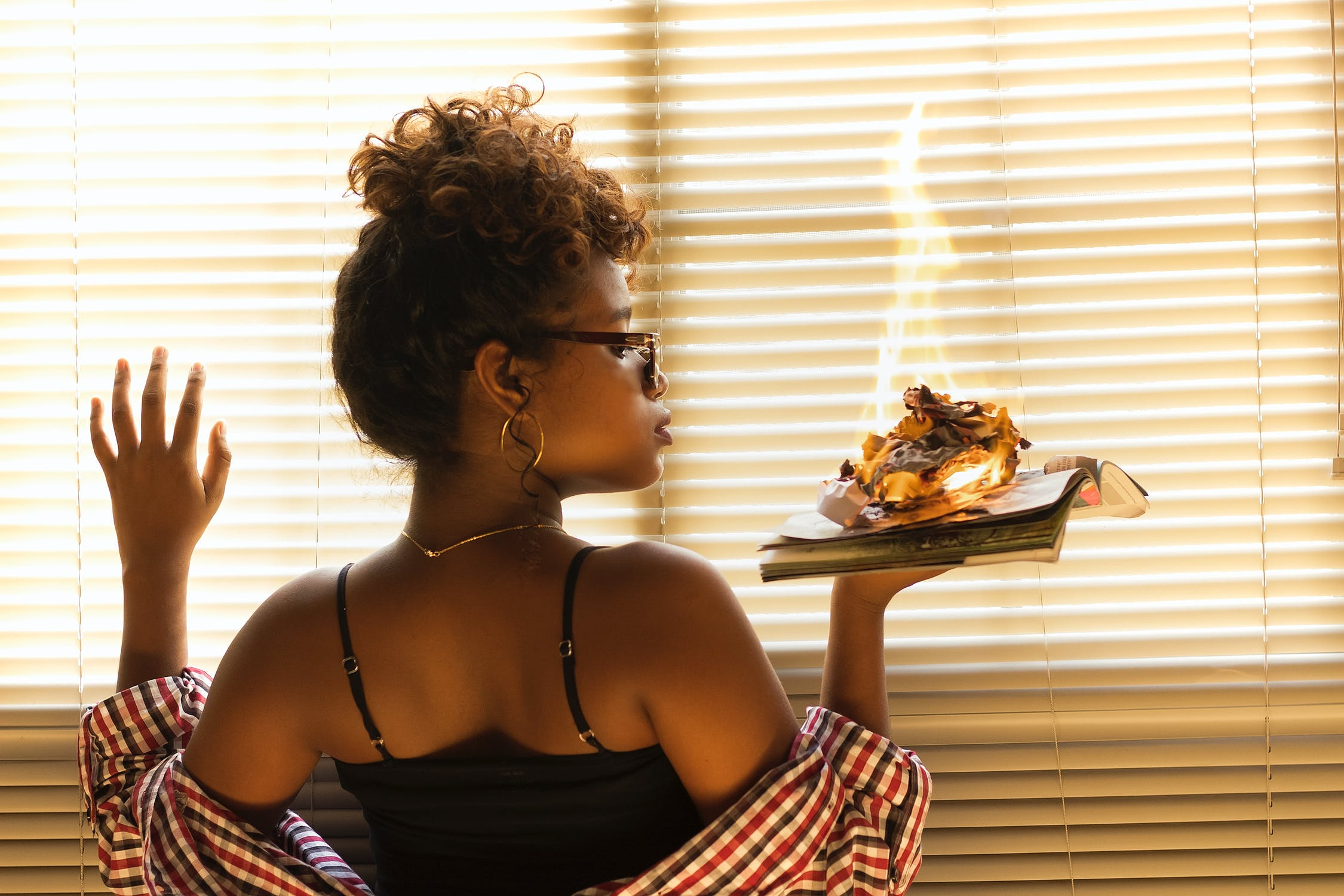 Black woman holding book with burning paper