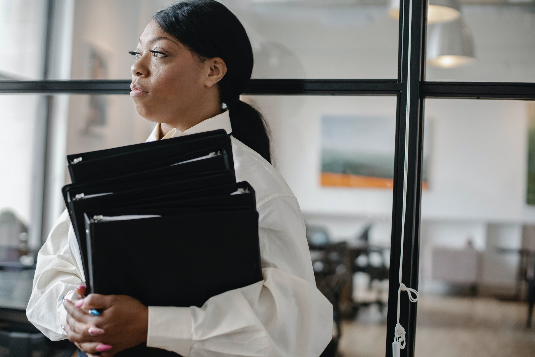 Black woman standing with files in hand