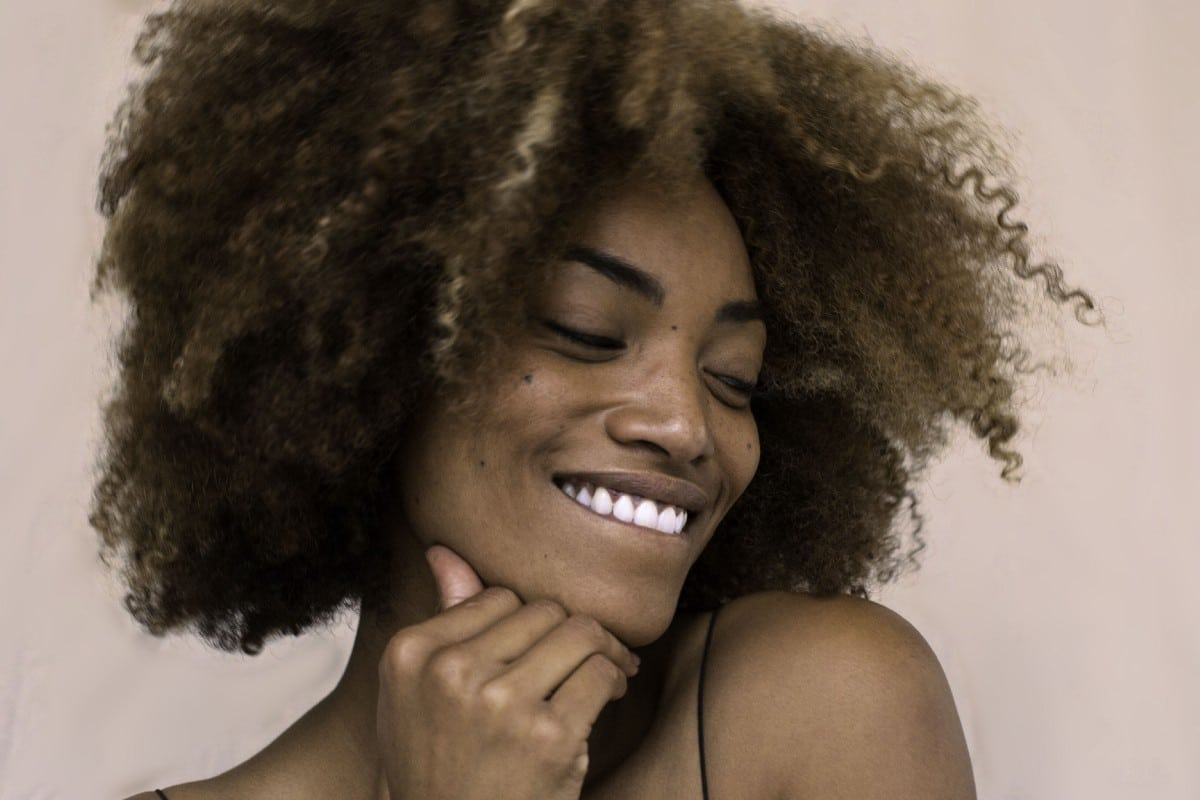 black woman with curly afro hair smiling