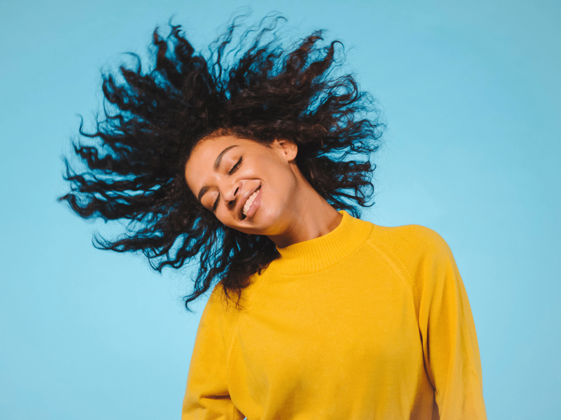 happy black woman wearing yellow sweater