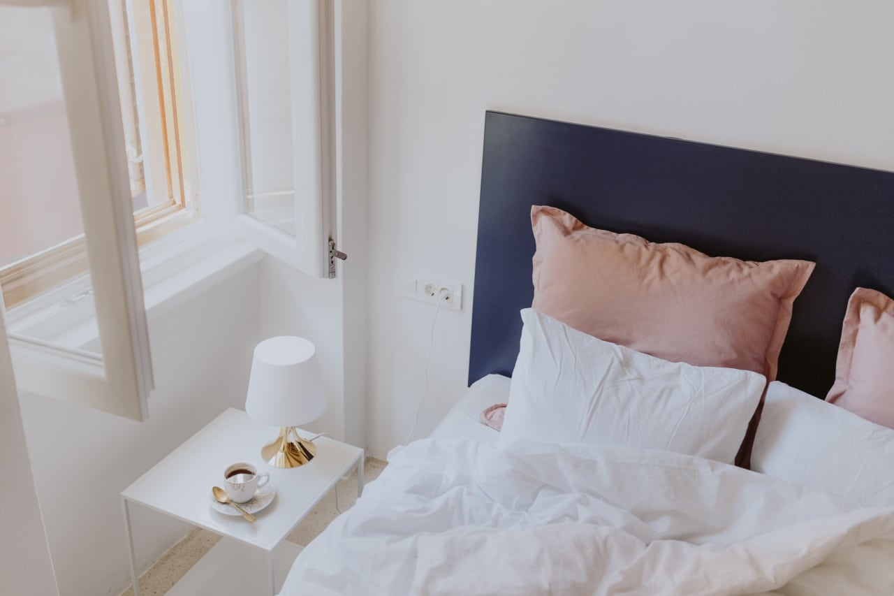 White bedroom interior with window, coffee and small lamp on side table