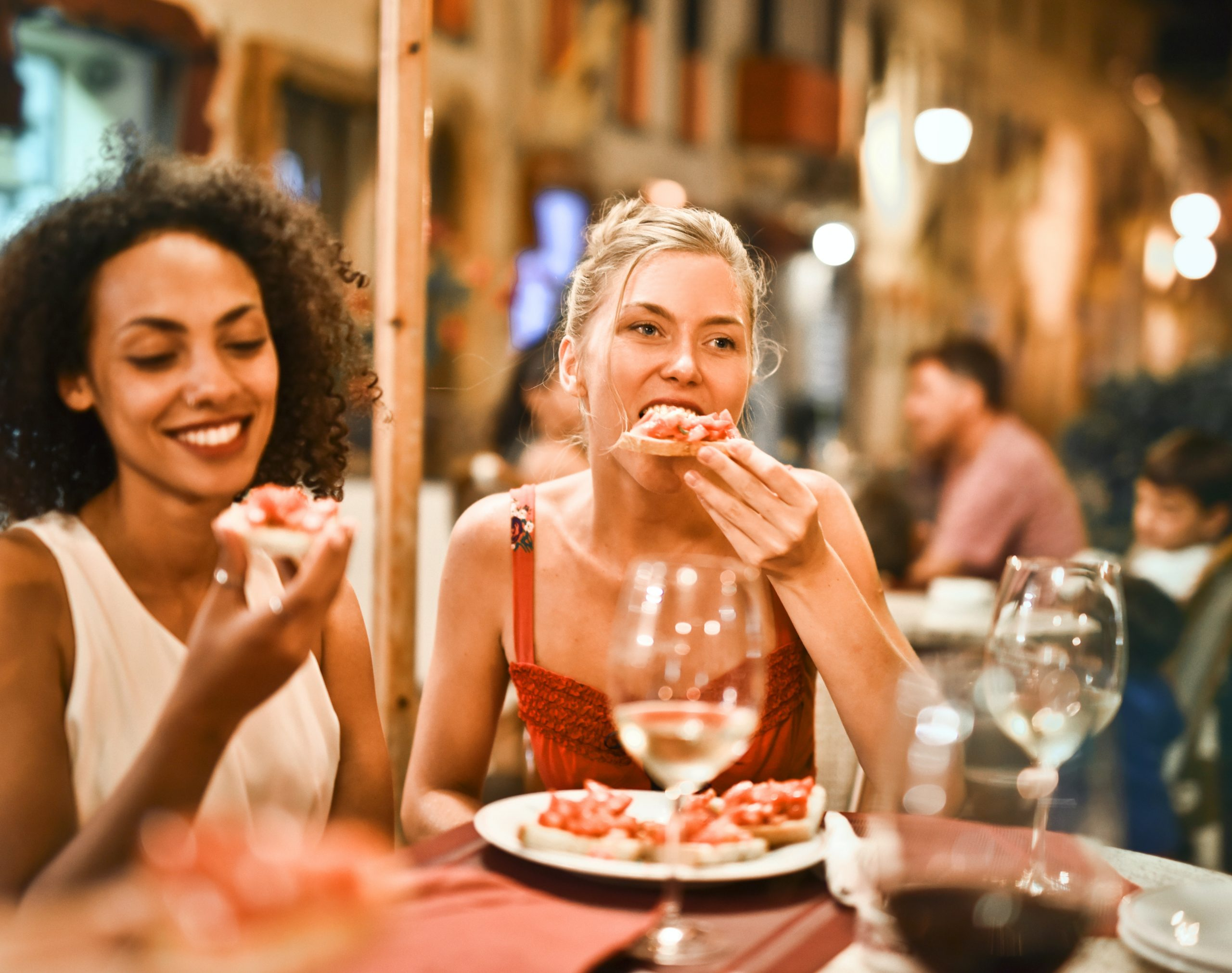 black woman eating at resteraunt socially with friend