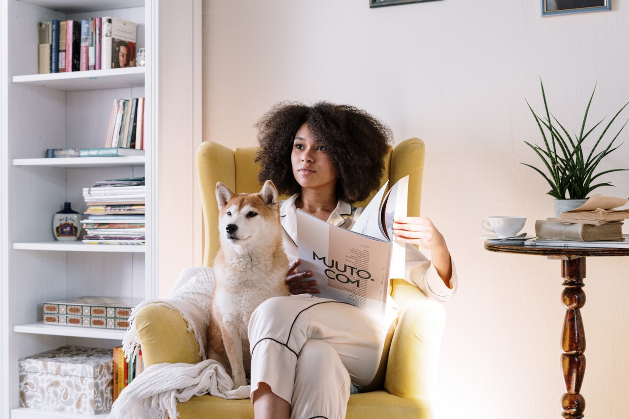 black woman watching tv with pet