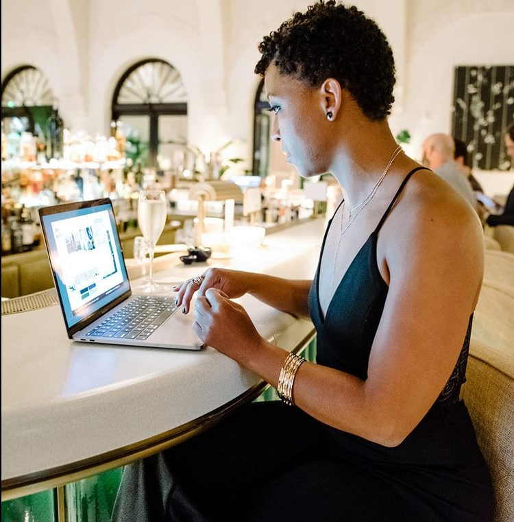 black-woman-shana-robinson-working-from-bar-laptop-typing